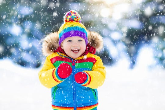Child playing with snow in winter.