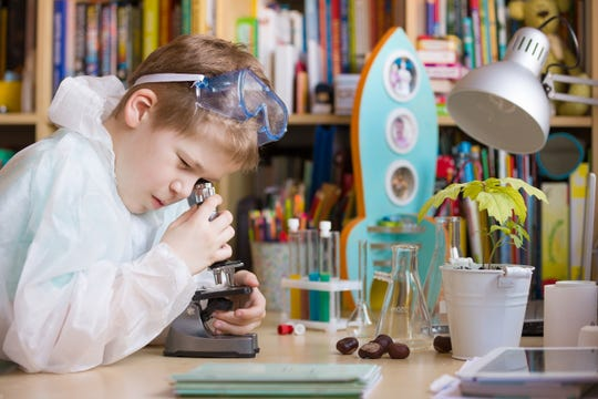 Elementary school boy looking into microscope at his desk.