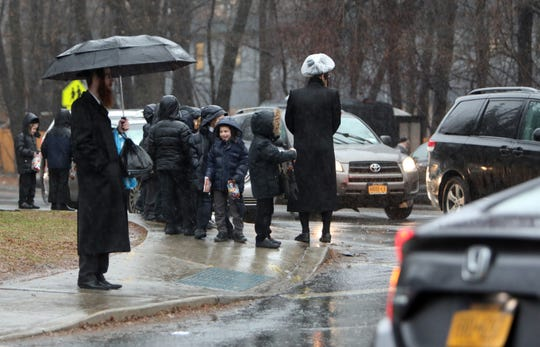 Orthodox Jewish students wait at the intersection of Route 306 and Maple Avenue in Monsey after being let out from school Dec. 30, 2019.