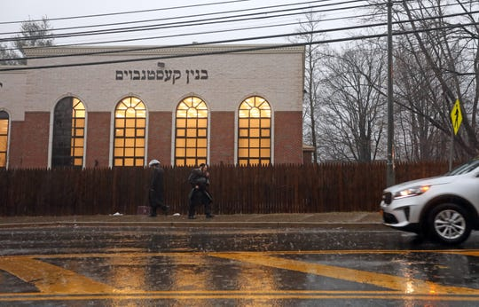 Orthodox Jewish men walk on Maple Avenue in Monsey on a rainy afternoon Dec. 30, 2019.