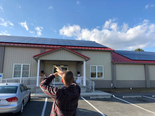 Businessman Richard Spinks shields his eyes from the sun as he counts the solar panels on the roof of his Gigglebugs early learning center in Millsboro, Del., on Wednesday. Dec. 18, 2019.
