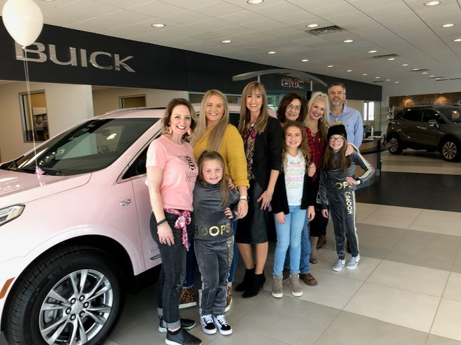 Wendy Masterson, center in black, is seen with friends and family as see accepted her new pink Cadillac for achieving an exceptional Mary Kay sales level.