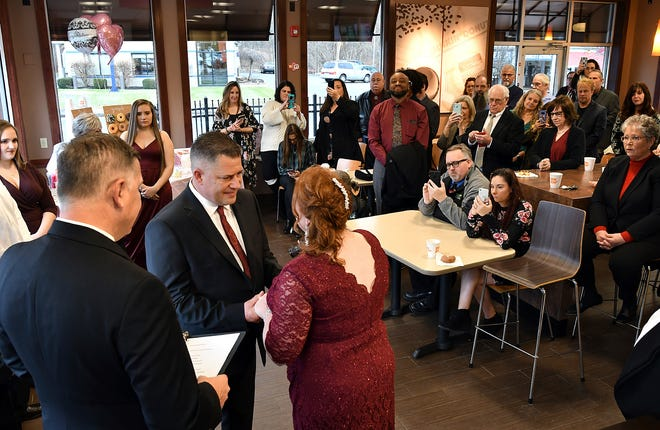 Jason Roy and Valerie Sneade say their vows in front of friends and family at the Dunkin' Donuts on Friday, Dec. 27, 2019 in Worcester, Mass.  The couple reunited for their wedding vows at the Dunkin' Donuts where their young love splintered nearly thirty years ago.