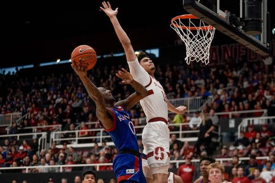 Kansas Jayhawks guard Marcus Garrett  attempts to score against Stanford Cardinal forward Jaiden Delaire during the second half at Maples Pavilion in Stanford, Calif.