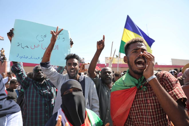 Sudanese people react as they gather in front of a court in Omdurman, near the capital Khartoum, Sudan, 30 December 2019, during the trial of a group of intelligence agents who are accused of the death of a school teacher while in custody.