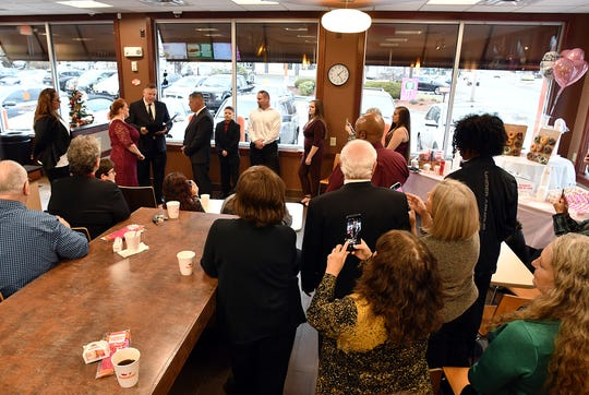 Jason Roy and Valerie Sneade say their vows in front of friends and family at Dunkin' Donuts on Dec. 27 in Worcester, Mass.