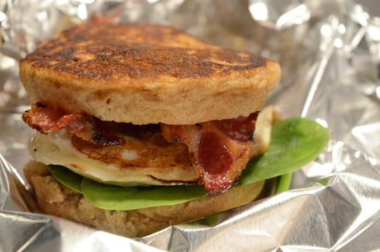 A breakfast sandwich with eggs, spinach and bacon can be eaten on the run once wrapped in foil.