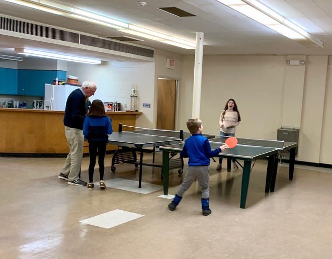 Bernie Sanders plays ping pong with his grandchildren, Ella, Dylan and Tess, at St. Marks church on Christmas Eve