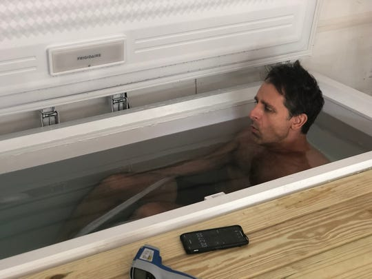 Jonathan Greenfield, a 49-year-old Cherry Hill native with ALS, soaks in a homemade ice bath he uses for meditation. He practices a method developed by Wim Hof.