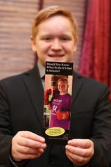 Paul St. Pierre, 13 of Maple Shade shows one of the bookmarks that the Anita Kauffman Foundation had made for him to support his fight for epilepsy awareness.
