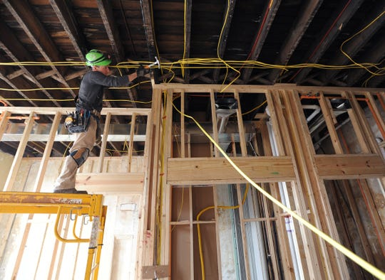 Ron Sutphin, with Chelser Construction, runs electrical wiring for a ceiling fan in the Carlisle Building.