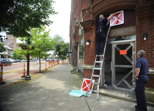 "Chillicothe Assistant Fire Chief Steve Gallagher hangs a red ""X"" sign over what once was the main entrance to the Carlisle building. Gallagher was assisted by Capt. Jeff Creed. Gallagher said the sign will warn firefighters not to enter the building in the event they respond to a fire there."