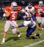 Westfall quarterback Trent Williamson (5) evades a tackle by Unioto's Jon Bowman to pick up a first down in the first half of a Scioto Valley Conference game in September of 2012. Williamson shared co-offensive back of the year honors with Piketon's Isaac Brabson.