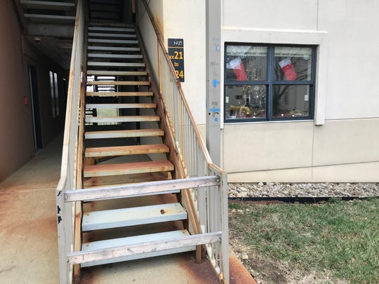 A wood barricade blocks the front part of an exterior staircase at Woodcrest Apartments on Northern Kentucky University's Highland Heights campus. NKU is closing the apartments immediately because of structural deterioration.