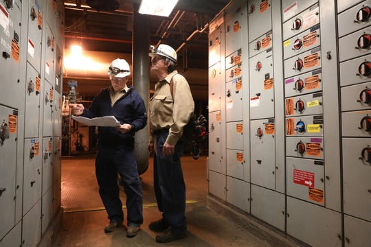 Ray Durben, right, and Keith McCoy talk about a piece of equipment in AEP's Conesville plant recently. Both men were retired, but came back to work to help close the plant as other employees found work elsewhere.