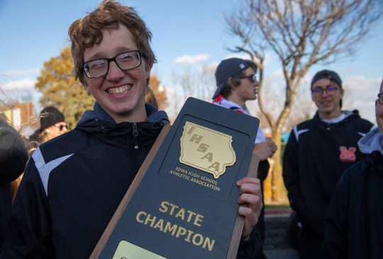Noah Moore, a junior at Madrid High School and a member of the school's cross country team, helps celebrate the team's state championship this past fall. Moore was killed in a car crash in Hardin County on Monday.