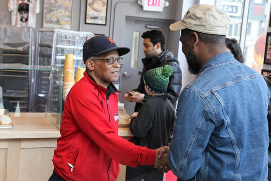 Owner Herman Hayes, left, greets guests during opening day at Dilla's Delights donut shop.