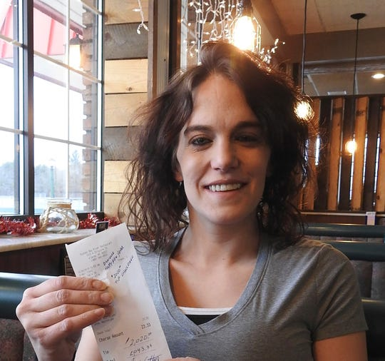 """In this Dec. 30, 2019, photo, server Danielle Franzoni holds a receipt from a customer with a $2,020 tip included at Thunder Bay River Restaurant in Alpena, Mich. The credit card receipt said """"Happy New Year. 2020 Tip Challenge."""" Franzoni, a single mother, couldn't believe the number, but her manager assured her the tip was legitimate. She said she was living in a homeless shelter a year ago. Franzoni plans to use the money to reinstate her driver's license and build savings."""