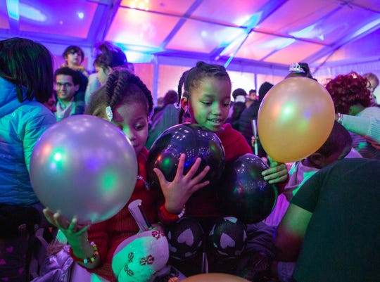 Kids reach for balloons during a New Year's Eve Balloon Drop at Beacon Park in Detroit, Tuesday, Dec. 31, 2019. Hundreds gathered to dance and have their face painted, leading up the balloon drop.