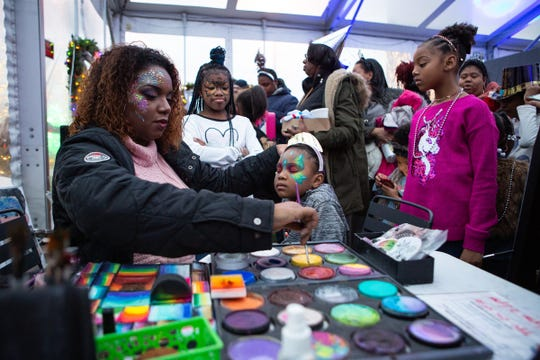 Dominique House paints hundreds of faces during a New Year's Eve Balloon Drop at Beacon Park in Detroit, Tuesday, Dec. 31, 2019.