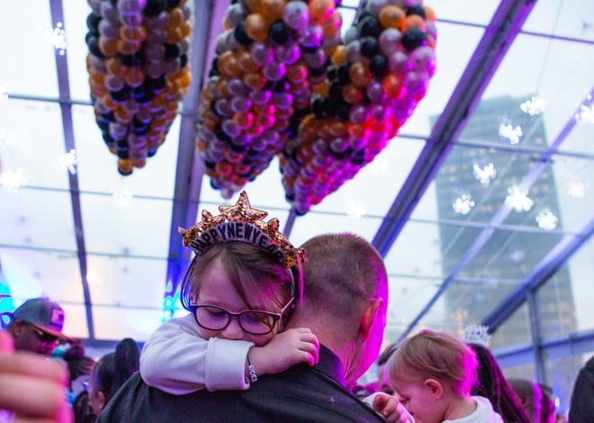 Noelle Edwards, 6, of Romulus, rests on her dad Mark during a New Year's Eve Balloon Drop at Beacon Park in Detroit, Tuesday, Dec. 31, 2019.