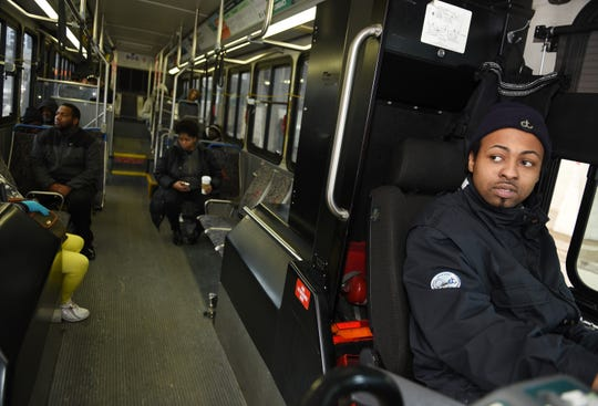Jerome Conner, 28, looks in his rearview mirror before leaving for his Fenkell Avenue route from the Rosa Parks Transit Center in downtown Detroit.