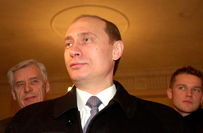 FILE - In this file photo taken on Sunday, March 26, 2000, acting Russian President and Presidential candidate Vladimir Putin talks with representatives of the news media at a polling station in Moscow, Russia.
