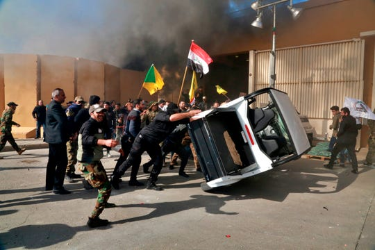 Protesters damage property inside the U.S. embassy compound, in Baghdad, Iraq, Tuesday, Dec 31, 2019. Dozens of angry Iraqi Shiite militia supporters broke into the U.S. Embassy compound in Baghdad after smashing a main door and setting fire to a reception area, prompting tear gas and sounds of gunfire.