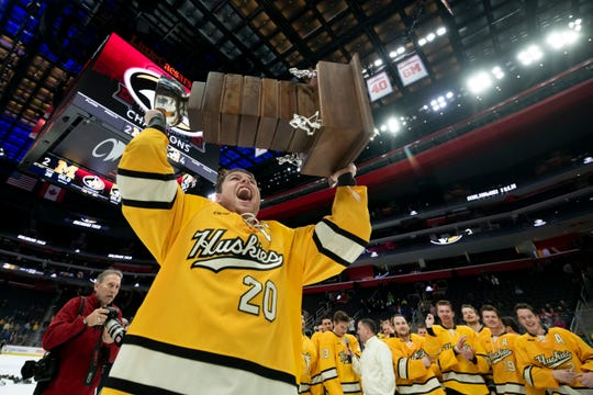 Michigan Tech forward Alex Smith lifts the MacInnes Cup after the Huskies defeated Michigan 4-2 during the championship game of the Great Lakes Invitational.