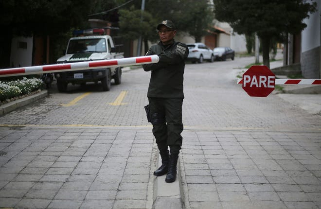 A police officer stands at the entrance leading to the residence of Mexico's ambassador to help make sure nine former officials from the government of deposed Bolivian President Evo Morales, who have taken refuge inside, do not leave the country, in La Paz, Bolivia, Monday, Dec. 30, 2019.