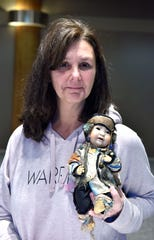 Debbie Savalle, of Dryden, poses with a porcelain doll from Queen Elizabeth II's nursery, gifted to her grandmother when she was 3 years old.