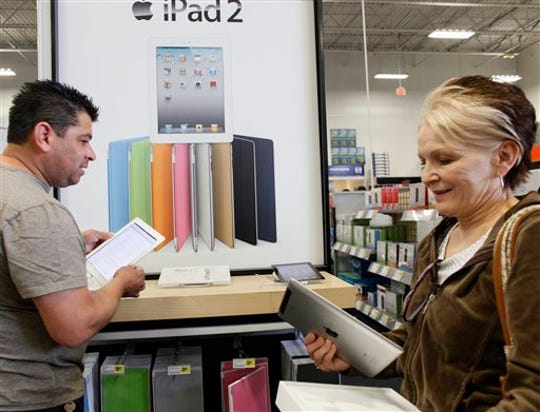 In this April 6, 2011 photo, Leticia Lozano, right, shops for a case for her new Apple iPad 2 tablet at Best Buy in Glendale, Calif. U.S. consumer confidence slipped ever so slightly in December, as expectations fell about economic growth over the next six months.