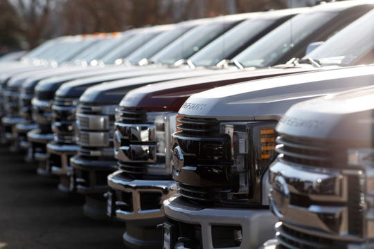 A row of 2020 Ford Super Duty pickups sits at a dealership.