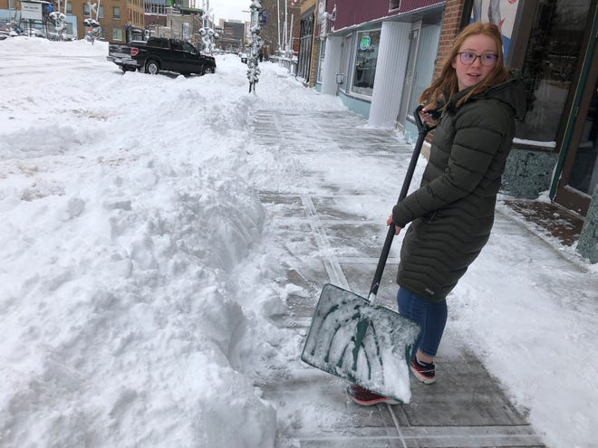 Volunteers help a woman dig out her parked car on Monday, Dec. 30, 2019, after it was blocked by snow from a plow that was clearing snow in downtown Fargo, N.D., after a blizzard that dumped a foot or snow in some areas of the metropolitan area.