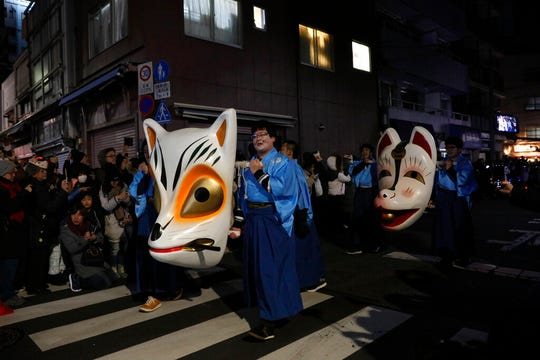 People carry large fox masks during a parade held to celebrate the New year Wednesday, Jan. 1, 2020, in Tokyo.
