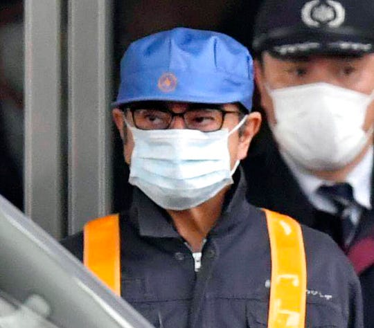 In this March 6, 2019, file photo, a masked man, front with blue cap, believed to be former Nissan Chairman Carlos Ghosn, leaves Tokyo's Detention Center in Tokyo. Former Nissan chairman Carlos Ghosn, who is awaiting trial in Japan on charges of financial misconduct, has arrived in Beirut, a close friend said Monday, Dec. 31, 2019. He apparently jumped bail. It was not clear how Ghosn, who is of Lebanese origin and holds French and Lebanese passports, left Japan where he was under surveillance and is expected to face trial in April 2020.