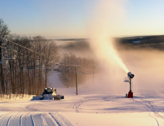 One machine grooms the slopes while another makes snow at Treetops Resort in Gaylord.