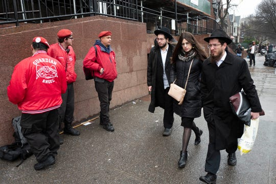 Members of the Guardian Angels, left, a volunteer safety patrol organization, stand in front of the Chabad Lubavitch World Headquarters, Monday in the Brooklyn borough of New York. The Guardian Angels and police have increased patrols in the Crown Heights neighborhood following an anti-Semitic attack on a Hanukkah celebration in Monsey, N.Y.