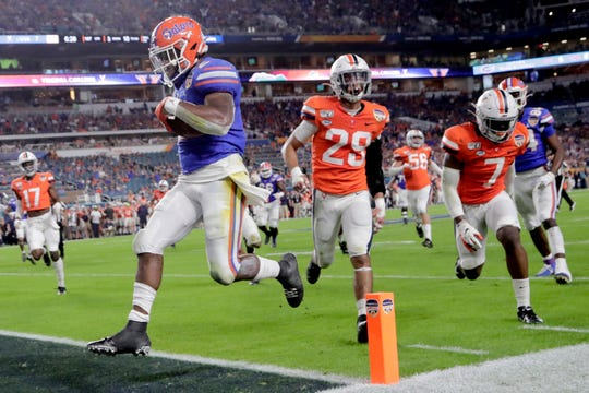 Florida running back Lamical Perine, left, runs past Virginia safety Joey Blount (29) to score a touchdown during the first half on Monday.
