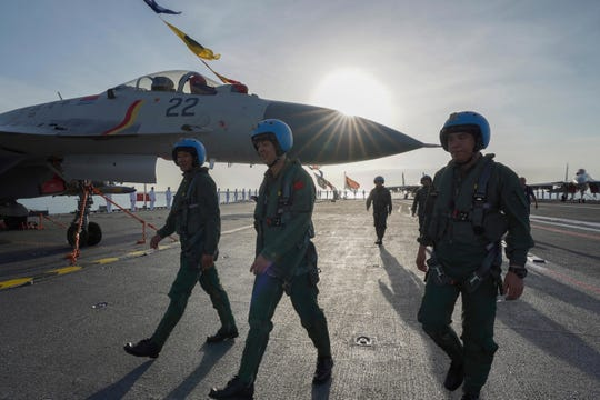 In this photo taken Dec. 17, 2019 and released Dec. 27, 2019 by Xinhua News Agency, pilots walk on the deck of the Shandong aircraft carrier at a naval port in Sanya in southern China's Hainan Province.