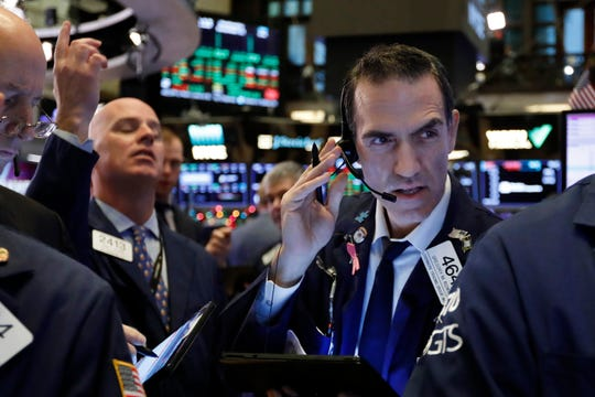 Trader Gregory Rowe, right, works on the floor of the New York Stock Exchange, Wednesday, Dec. 11, 2019.