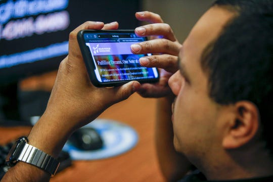 Jose Martinez tests a website on his phone for its accessibility to visually impaired people at Chicago Lighthouse on November 19, 2019. Martinez, who is legally blind, works for the Lighthouse's accessibility consulting project, which helps businesses make sure their websites meet global accessibility standards.