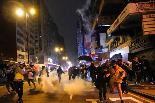 Protesters react as police fire tear gas during a demonstration in Hong Kong, early Wednesday, Jan. 1, 2020.