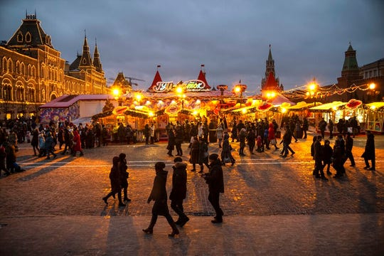 People walk at Holiday's Market on Red Square, decorated for New Year and Orthodox Christmas celebrations in Moscow, Russia, Monday, Dec. 30, 2019.