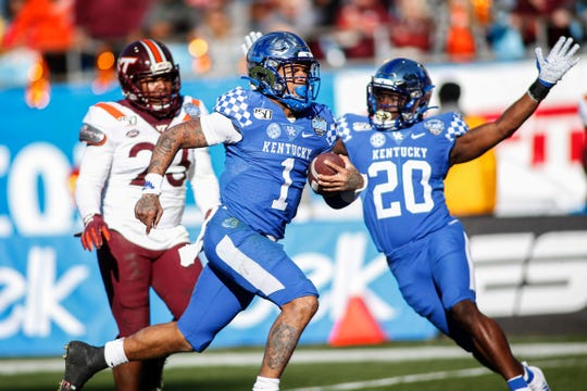 Kentucky quarterback Lynn Bowden Jr. (1) rushes for a 61-yard touchdown against Virginia Tech in front of Kentucky running back Kavosiey Smoke (20) and Virginia Tech linebacker Rayshard Ashby (23) in the second half on Tuesday.