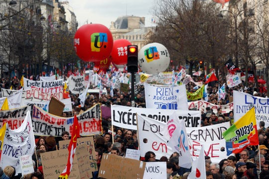 FILE - In this Dec. 17, 2019, file photo, protestors march in Paris. Unions represent less than 10% of salaried workers but have a cozy, if paradoxical, relationship with officialdom that empowers them to block change.