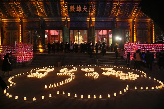 "Buddhists light candles to form letters meaning, ""Best wishes for a Happy New Year,"" during New Year celebrations at Jogyesa Buddhist temple in Seoul, South Korea, Wednesday, Jan. 1, 2020."