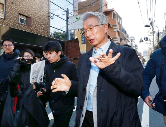 "Junichiro Hironaka, right, lawyer for Nissan's former chairman Carlos Ghosn, gestures to the media as he heads to his office in Tokyo, Tuesday, Dec. 31, 2019. Ghosn says from Lebanon he was not fleeing justice but instead left Japan to avoid ""injustice and political persecution"" over financial misconduct allegations."