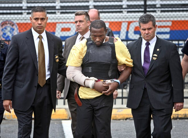 Darrell Fuller is escorted out of a police station in Mineola, N.Y., on Oct. 25, 2012. Fuller, who was serving a life sentence in prison, died earlier in the month at the Elmira Correctional Facility.