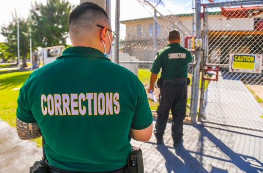 Two corrections officers prrpare to enter the Department of Corrections Hagåtña Detention Facilities on Tuesday, Dec. 31, 2019.